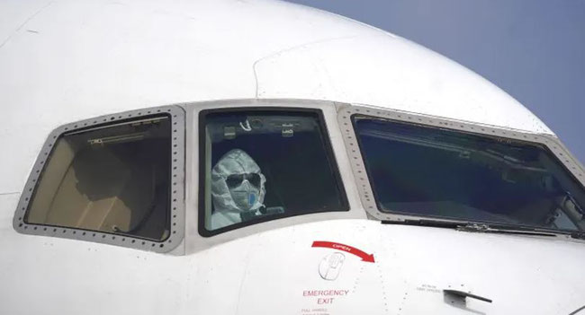 Pilot wearing protective suit in cargo plane at Wuhan Tianhe airport, China.  Image © Cheng Min/Xinhua/AP