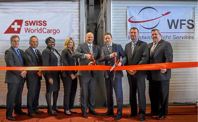 Master of scissors: Michael Simpson (left), EVP Americas, WFS / Michael Ganz, Head of Cargo Northeast USA + Canada, Swiss WorldCargo framed by their teams  -  courtesy Swiss / WFS