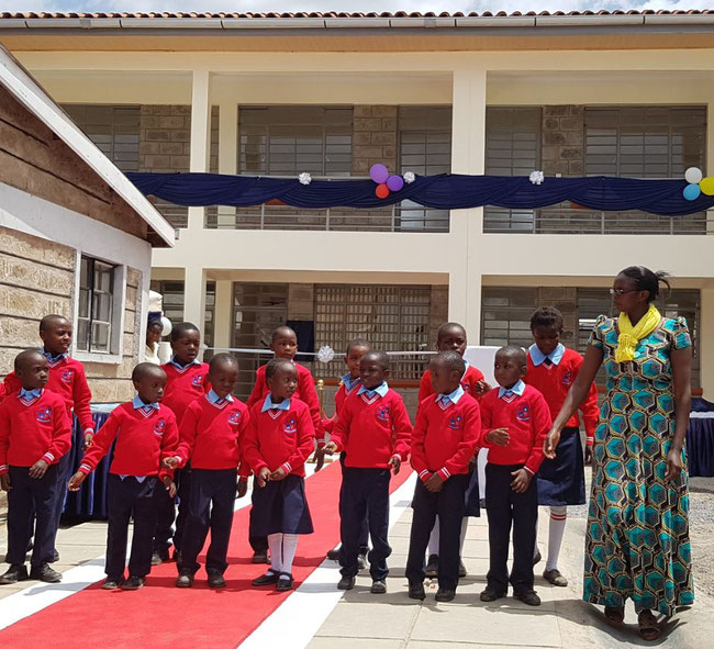 School children and their teacher Tabitha Njeri Njuguna are greeting the guests with singing and dancing brimming over with joy.