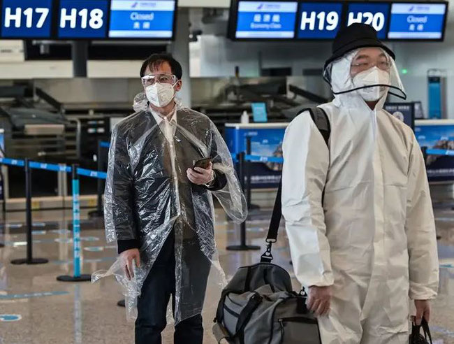 Passengers wearing protective gear walk at Wuhan's Tianhe Airport on April 8, after its reopening only hours before  -  image courtesy AFP