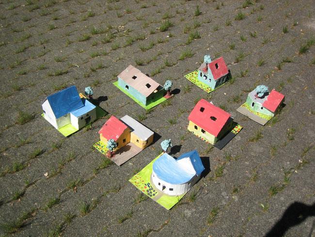 Häuser aus Pappe, bemalt. In einem kleinen Dorf zusammengestellt. In der Perspektive einer Luftaufnahme fotografiert.