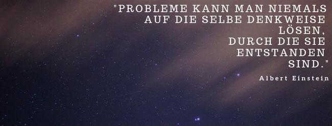 """Hier ist ein Bild mit einem Spruch: """"Probleme kann man niemals auf die selbe Denkweise lösen, durch die sie entstanden sind."""" von Albert Einstein. Im Hintergrund ist ein Sternenhimmel zu sehen."""