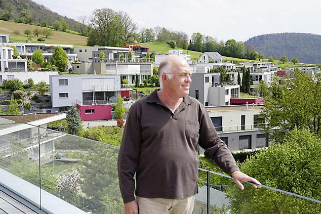 Architekt Peter Stocker in seinem Traumhaus in Frick, dahinter die von ihm entwickelte Frickberg-Überbauung.