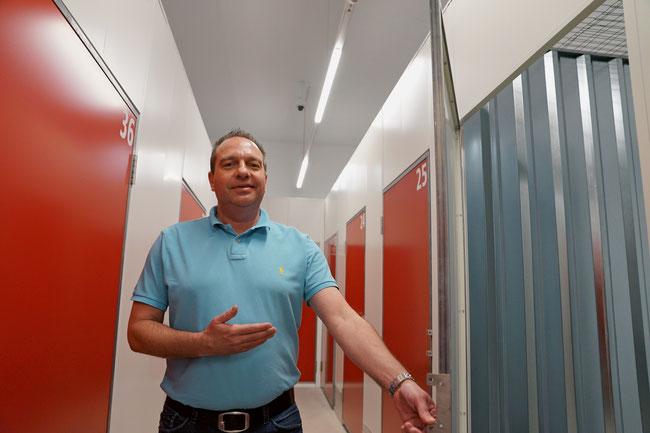 Marco Perlini vor einer geöffneten grösseren USB-Box., hinten an der Decke eine der Dauer-Videoüberwachungskameras.