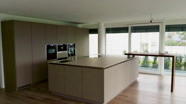 Eine Einzelanfertigung einer Traumküche nach Mass und mit integriertem Nussbaumholztisch aus dem Hause Schreinerei Leo Schmid AG in Wittnau.