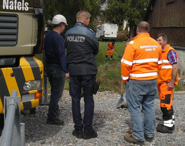 """Abräumen unter Polizeischutz. Sogar ein Mann von """"Nationalstrassen Gebiet VI"""", Zweiter von rechts, ist anwesend. Im Hintergrund ein Mitarbeiter des Bauamts beim Räumen. (Foto: Kurt Philipp Hauser)"""