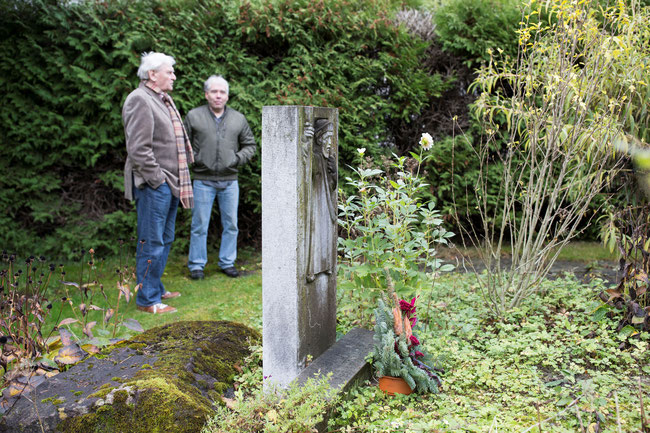 Im Garten des Linthhofs:  Letzte Ruhestätte für den Grabstein.  Wolfgang Hauser, Sohn von Dr. Fridolin Hauser-Zech, rechts, gewährt Zutritt zum Garten für Fotoaufnahmen des abgeänderten Grabsteins, der früher auf dem Friedhof Näfels stand.