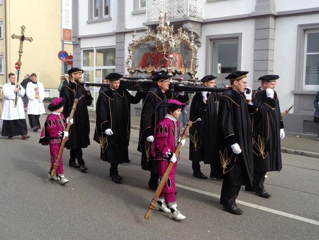 Seit Jahrhunderten wird am Grossen Fridolinsfest, der schwere Fridolinsschrein von acht kräftigen Männern durch die Innenstadt getragen. Zur Entlastungen und für Ruhepausen wird der Schrein auf die von Knaben mitgetragenen Stützen abgestellt.