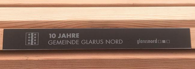 """Auf der Bank angebrachte Inschrift """"10 Jahre Gemeinde Glarus Nord"""""""