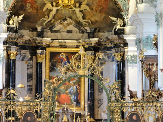 Über dem kunstvoll geschmiedeten und vergoldeten Gitter, das Schiff und Chor trennt das Wappen von Fürstabt Beda Angehrn. Er stiftete den Hochaltar für die Näfelser Hilariuskirche. Das nämliche Wappen prangt in Näfels zwischen Oberbild und Hauptbild.