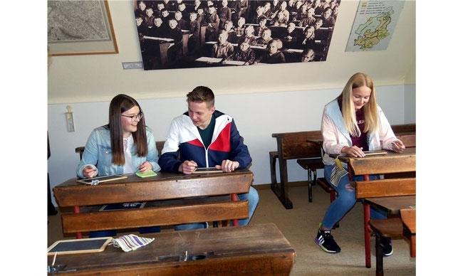 Anna (v. li.), Jan und Mirja haben das Smartphone gegen Schiefertafeln getauscht und spielen Stadt, Land, Fluss in der Schulstube.