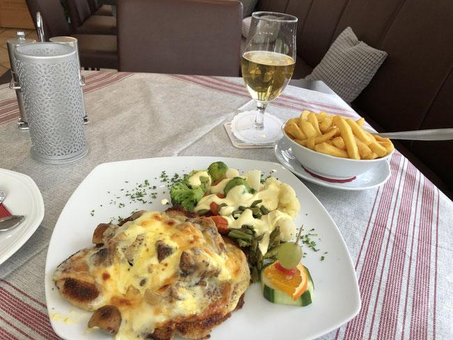 Schnitzel überbacken mit Käse und Champignons, mit Gemüse und Pommes und ein Radler