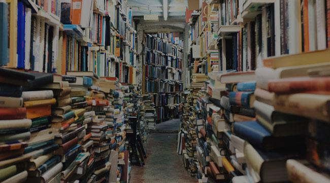 Biblioteca repleta de libros desordenados.
