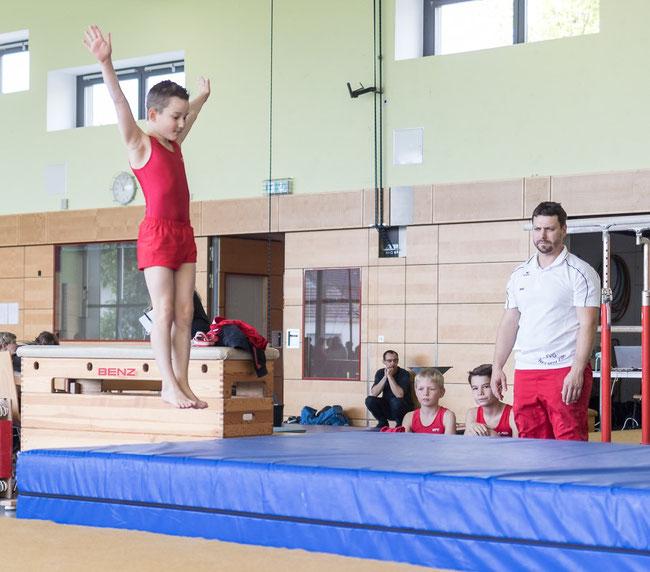 Damian Hein beim Sprung, Loic Rückert, Ilja Rolsing und Trainer Peter Siefert schauen zu.