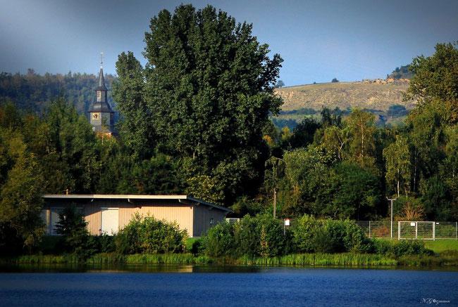 Bürgerhaus am See, sowie im Hintergrund die Pfarrkirche St. Johannes der Täufer und ein Teil der Abraumhalde des ehemaligen Steinkohlebergwerk Sophia Jacoba