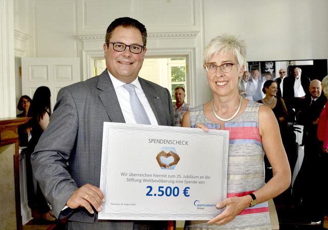 Patrick Döring gratuliert Renate Bähr zum Jubiläum und überreicht ihr den Spendenscheck der Wertgarantie-Gruppe.
