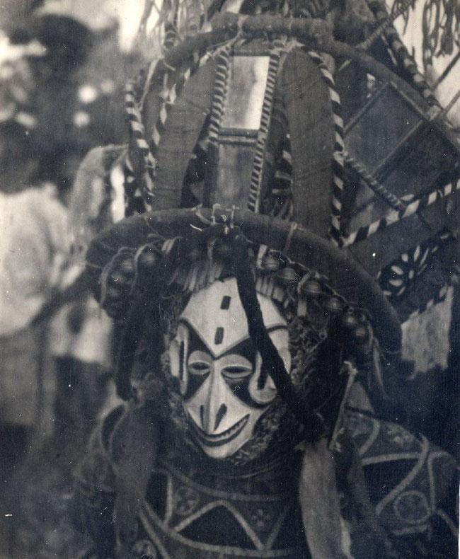 """Maschera femminile """"agbogho mmanwu"""" indossata da un ballerino maschio che enfatizza movenze e caratteristiche ideali della donna Igbo"""