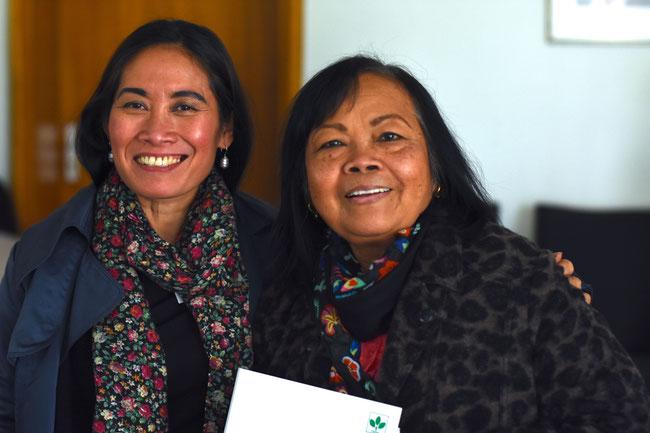 Zwei Menschen mit unterschiedlicher Hautfarbe schauen lächelnd in Kochkleidung in die Kamera