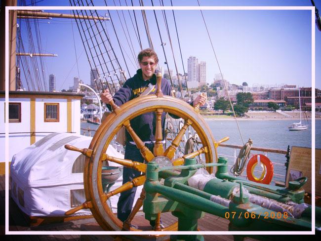 Guillaume Chérel sur le pont d'un bateau tient la barre