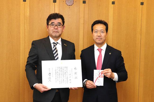 感謝状を手にするL.河上 哲会長と10万円の目録を手にする西川旭川市長