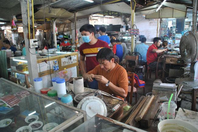Dieser Goldschmied stellt in Handarbeit Goldketten her. Im Hintergrund sieht man, wie viele Menschen hier arbeiten.