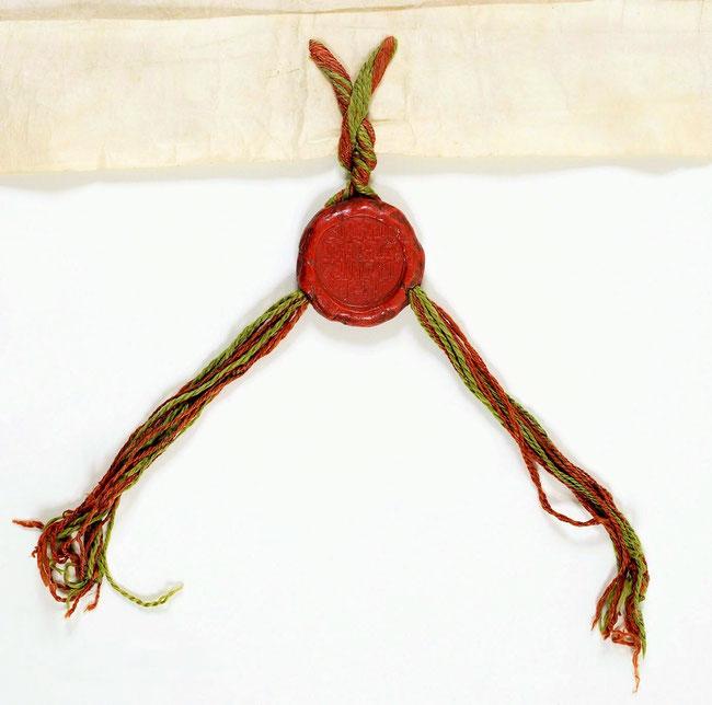 Sceau du bey de Tunis sur lacs de soie rouge et verte. Ce sceau n'est pas figuré il est couvert de texte en arabe. Il mesure 5,5 cm de diamètre.