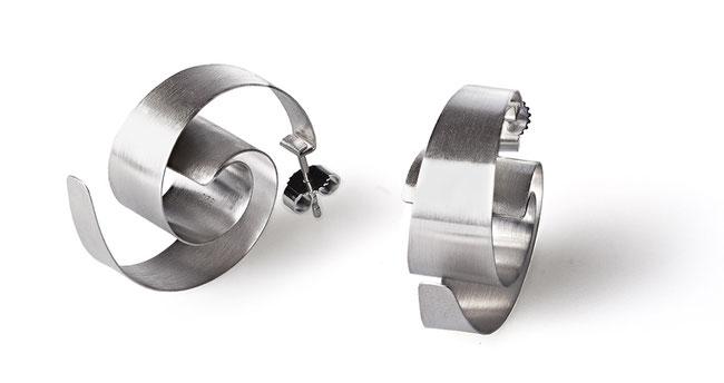 Die Ohrstecker ONDA aus seidig glänzendem Silber faszinieren mit ihrem raffinierten Spiel der Perspektive. Ihre Grundform bildet eine dreidimensional ausgearbeitete Spirale, die sich verändert, je nachdem, wie Sie den Ohrschmuck betrachten.