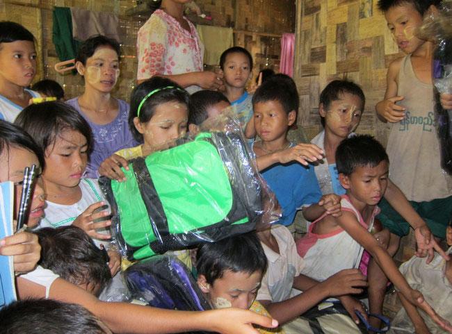 Distribution de fournitures scolaires (ici des cartables, stylos, etc.) à des enfants démunis pris en charges par PASDB.