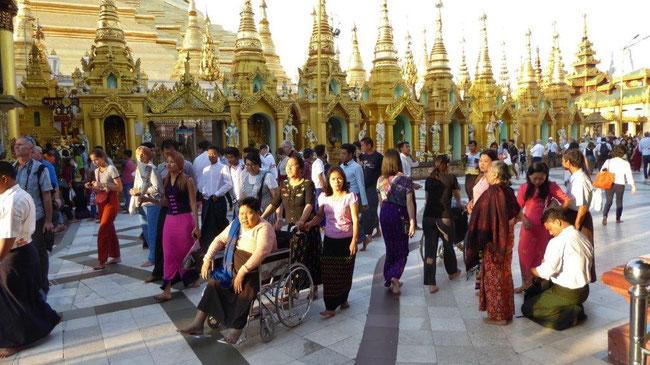 Bild: Foto zeigt die Shwedagon Pagode, um die viele Besucher herumfingern