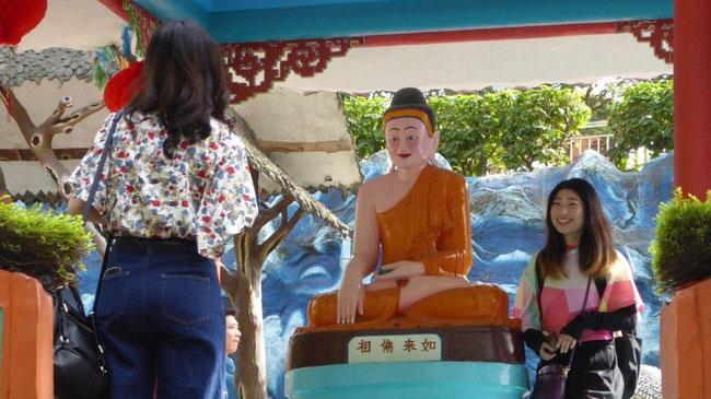Bild: Lachende Chinesinnen an einer Buddha Figur zur Fotografie
