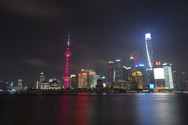 Deze foto van de skyline van Shanghai is gemaakt tijdens de Nationale dag van de Volkrepubliek China. Ter ere hiervan is de skyline extra rood verlicht en prijkt op diverse gebouwen de nationale vlag.