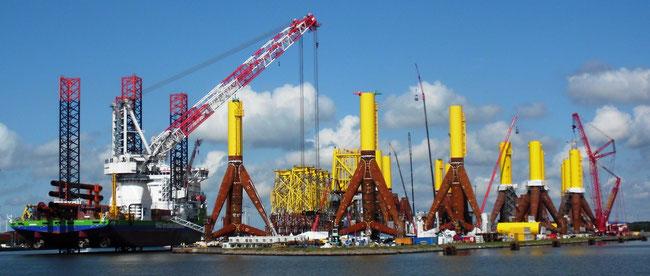 """Taufe des Errichterschiffes """"Innovation"""" in Bremerhaven, rechts stehen viele Tripods als Gründungen für Offshore Windanlagen (Foto Dr. Hochhaus)"""