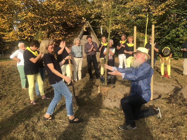 Gartenbotschafter John Langley fiel vor der Vorsitzenden der Stader Landfrauen,Monika Breuer, auf die Knie. Er war Ehrengast und Moderator bei der Pflanzaktion eines Bienenweidenbaums auf dem Holstschen Gelände in Fredenbeck.
