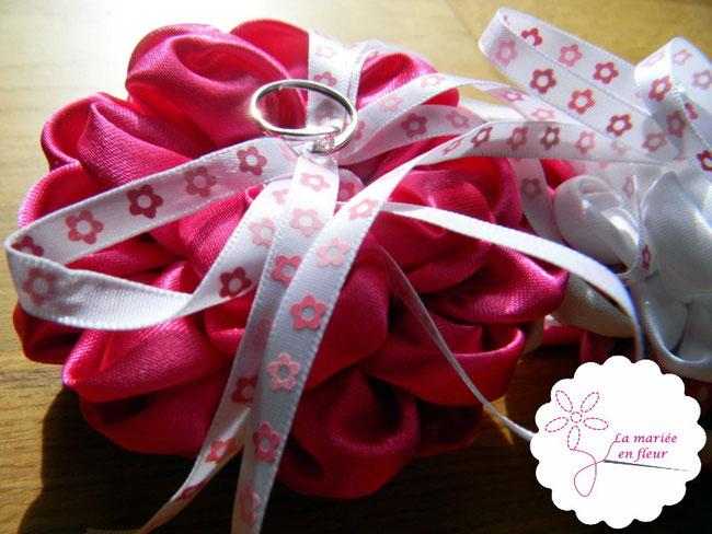 Bague de fiançailles posée sur coussin d'alliances en fleurs