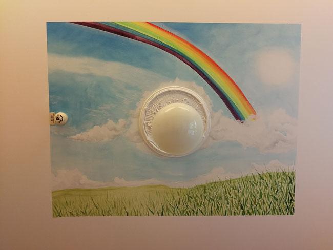 Himmel mit Regenbogen gemalt in einem Pflegezimmer an der Decke