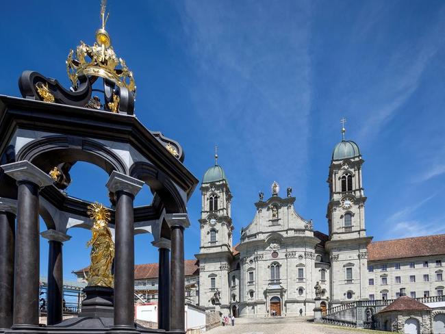 Kloster Einsiedeln mit Marienbrunnen auf dem Klosterplatz. Es heisst: wer aus allen 14 Röhren Wasser trinkt, erlöst eine Seele!