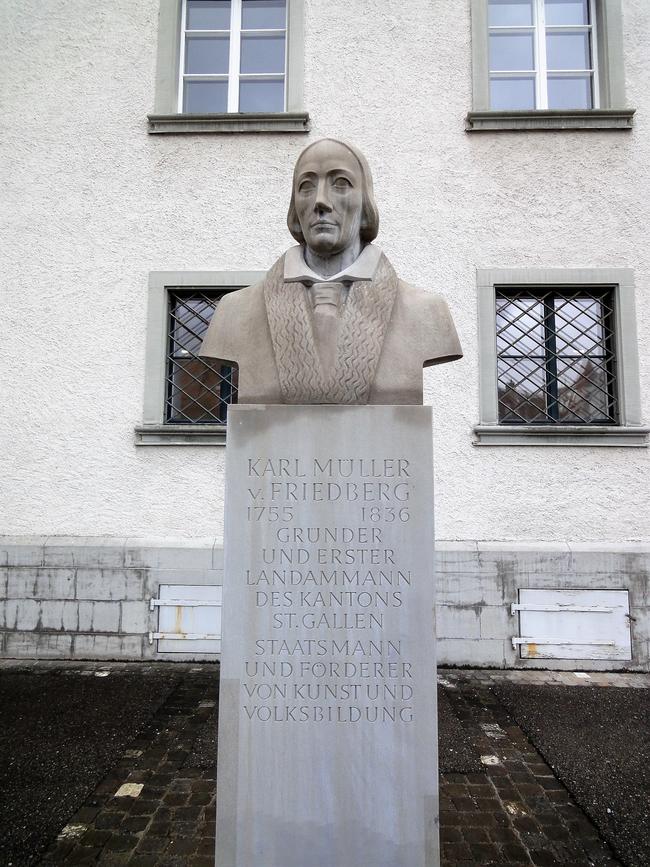 Inschrift: Karl Müller v. Friedberg 1755 1836 Gründer und erster Landammann des Kantons St. Gallen Staatsmann und Förderer von Kunst und Volksbildung. Gedenk-Stele im Bereich des Klosters und der Pfalz.