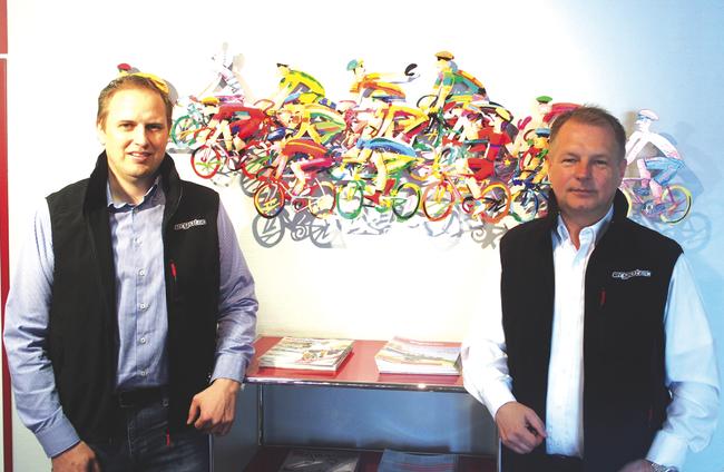 Wilhelm Humpert IV (rechts) und Prokurist Jens Stahlschmidt vor dem Fahrradgemälde im Eingang.