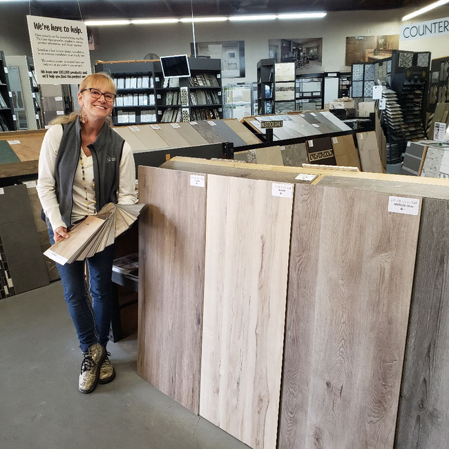 Tile Lines designer Lori holds a swatch book of LVT colors while standing next to large luxury vinyl tile planks of different colors.