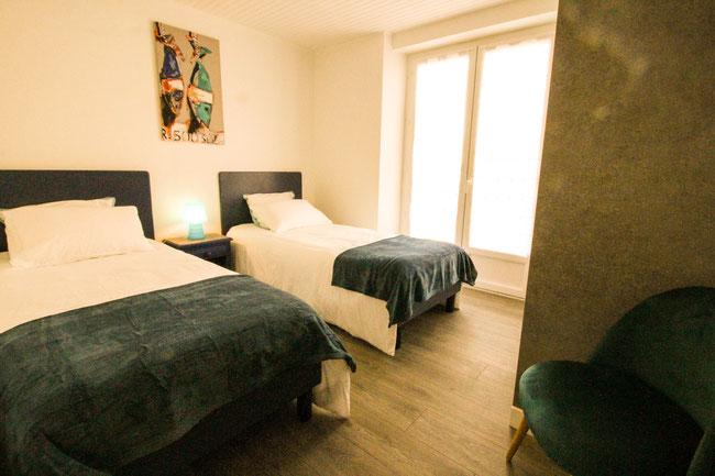 La chambre équipée de 2 lits, a une porte-fenêtre donnant sur la terrasse.