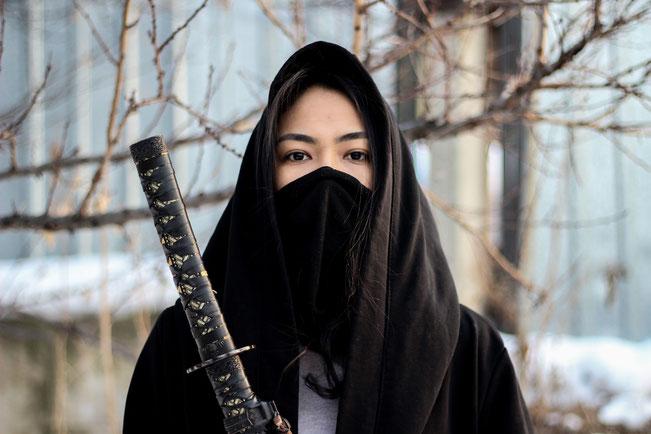 Eine asiatische Frau als Ninja gekleidet. Vor ihrem Körper hält sie ein Katana.
