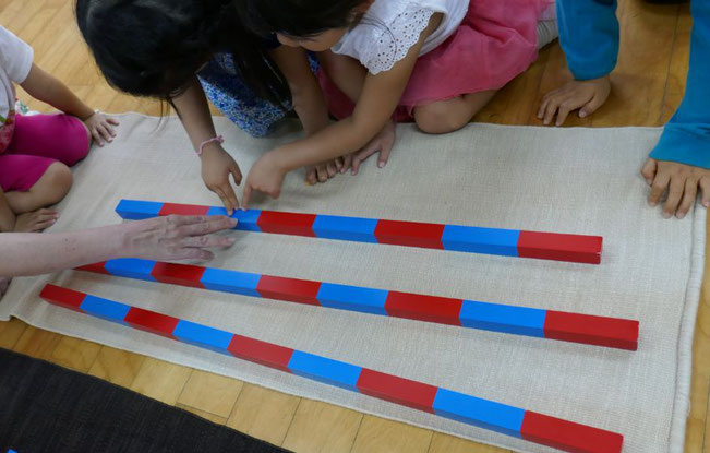 幼稚園児がモンテッソーリの活動で、算数の教具を使ってグループで活動しています。