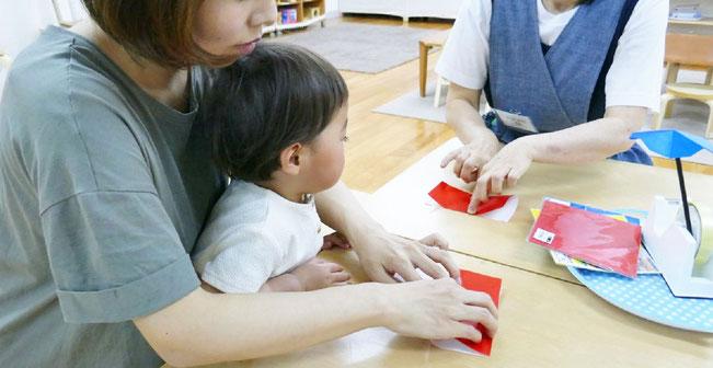 モンテッソーリの活動で、1歳児がお母さまといっしょに折り紙の活動を行っています。