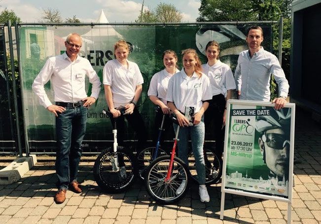 Martin Linder, Prokurist der Firma Theodor Elbers GmbH & Co. KG (li.), und Gideon Schwarze, 1. Vorsitzender des Radsportvereins Münster, mit den Einrad-Fahrerinnen vor dem Einsatz in Amelsbüren.