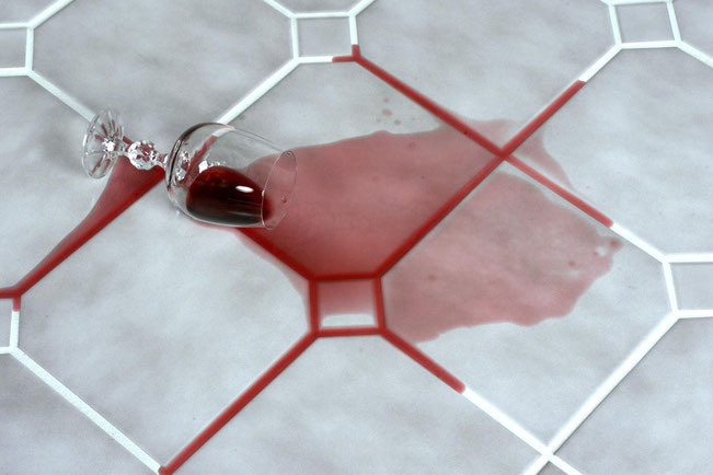 Wine spilled on a gray tile floor with white grout.
