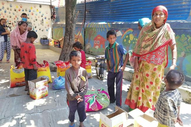 Familie mit Kindern in Kathmandu beim abholen von Lebensmittel Unterstützungspaketen
