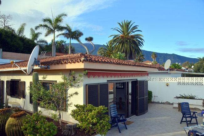 Ferienhaus in Bungalow-Form mit Palmen und dem Teide im Hintergrund.