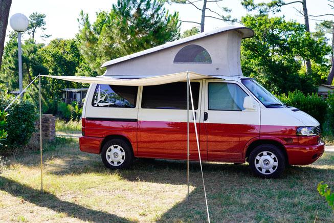 Rot, weißer Volkswagen California mit Markise und Aufstelldach