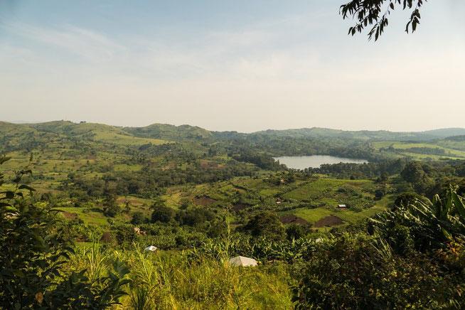 """Blick über die Hügellandschaft mit dem Crater Lake """"nyabikere"""" im Hintergrund"""