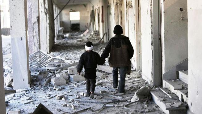 Kinder in Syrien gehen durch eine zerstörte Schule. © AP/dpa